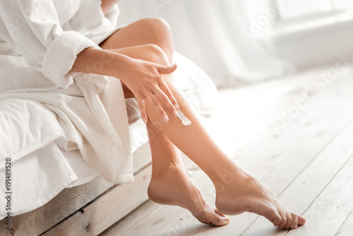 For soft skin. Close up of a female leg with moisturizing cream being applied on it