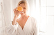 Quadro Fresh energy. Happy delighted nice woman holding an orange half and smiling while using it for cosmetic procedures
