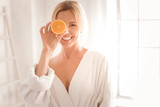 Fresh energy. Happy delighted nice woman holding an orange half and smiling while using it for cosmetic procedures - 191489717