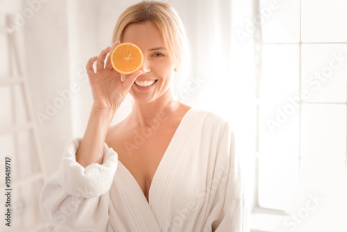 Fresh energy. Happy delighted nice woman holding an orange half and smiling while using it for cosmetic procedures