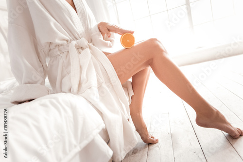 Full of vitamins. Close up of an orange half being pressed to a leg of a beautiful slim young woman
