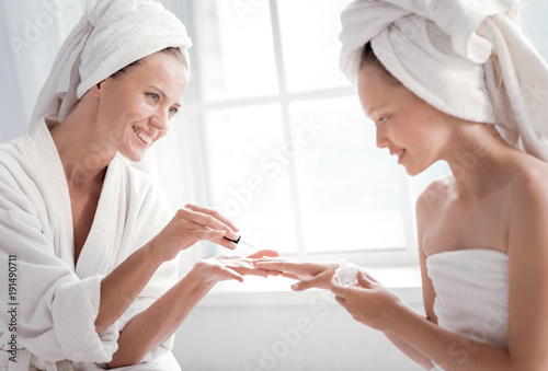 Staande foto Manicure Beauty procedure. Delighted happy attractive woman looking at her daughter and smiling while painting her nails