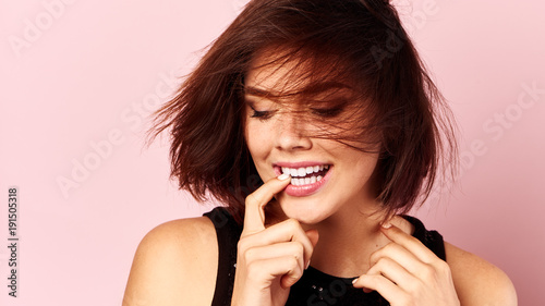 In de dag Kapsalon Cute girl with stylish haircut smiling over pink background.