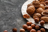 Different nuts on dark stone table. hazelnut,  walnuts - 191507769
