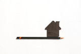small black model of a house with black pencil on a white background - 191510354