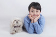 niño tumbado junto a su perro sobre fondo blanco