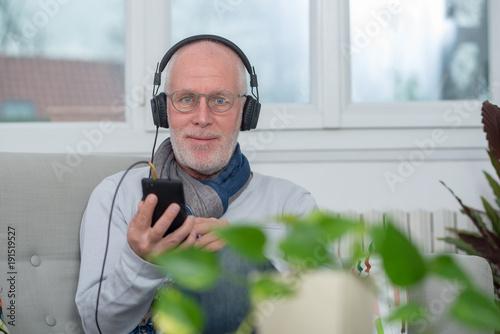 Fotobehang Muziek senior man in headphones listening to music at home