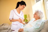 Beautiful nurse holding hand of old senior patient and comfort her - 191522973