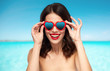 woman with heart shaped shades over sea and sky