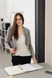 Young woman standing over binder in office - 191527334