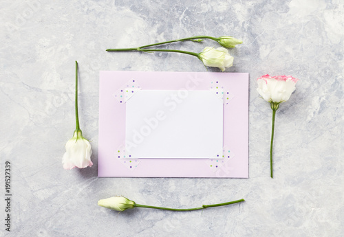 An arrangement of flowers and paper cards on gray background