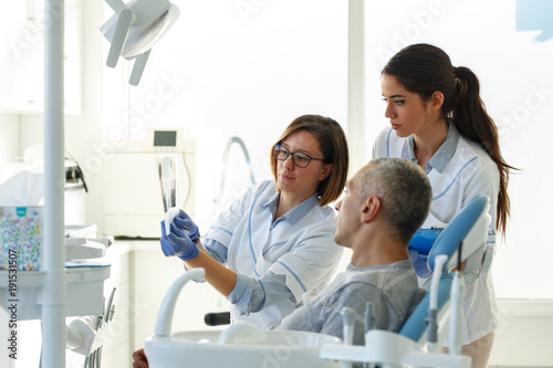 Fototapeta Dentist and her assistant in dental office talking with male patient and preparing for treatment.Examining x-ray image.