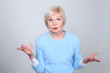 Senior woman 70 years of age is surprised face. She shows a gesture of surprise and bewilderment.
