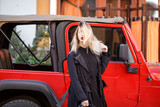 Street fashion concept. Trendy look of stylish young blond woman in black fashion coat and hat. Young lady standing over red car. Sunny spring or autumn weather. - 191544976