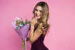 Charming, pretty girl is holding a big tulip bouquet in hands.. Pink background. Happy woman's day - 191550560