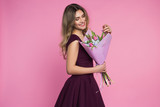 Fototapety Charming, pretty girl is holding a big tulip bouquet in hands. Pink background. Happy woman's day