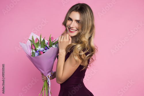 Fototapeta Charming, pretty girl is holding a big tulip bouquet in hands.. Pink background. Happy woman's day