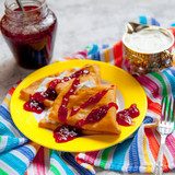 Two thin pancakes, folded in triangles, are poured with sour creamand raspberry jam. The concept of bright sweet breakfast. - 191551569