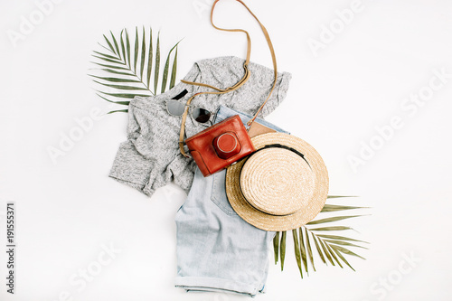 Woman fashion travel flatlay. Retro camera, straw, shorts, sunglasses and tropical palm leaf. Top view, flat lay.