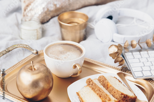 Fototapeta Cozy composition with tray and breakfast in bed. Still life background with gold decorations