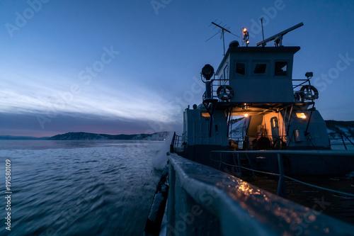 Fotobehang Schip The ferry sails along Lake Baikal on a winter evening