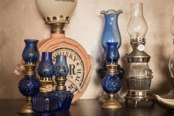 Few old-style kerosene lamps on shelf