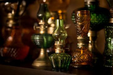 Small green kerosene lamp on background of other lamps