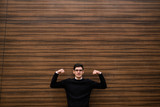 strong business solutions. development strategy. office corporate man showing his strength with hand gesture. wood texture wall background. outdoors street. free space concept - 191590150