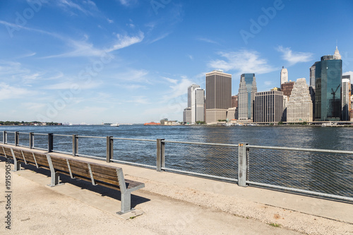 The famous riverside promenade in Brooklyn with the Manhattan business district in the background across the East river in New York city on a sunny day in the USA