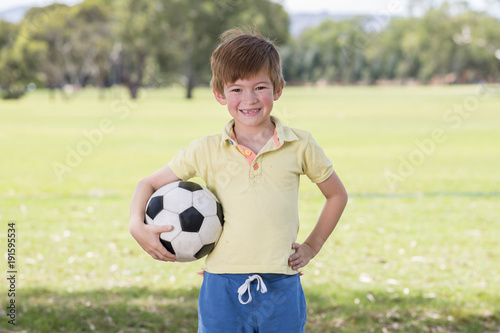 Poster young little kid 7 or 8 years old enjoying happy playing football soccer at gras