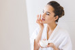 portrait of beautiful woman in bathrobe applying face cream