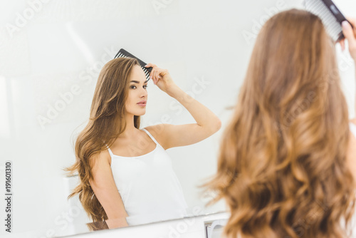 beautiful woman brushing hair with comb in bathroom