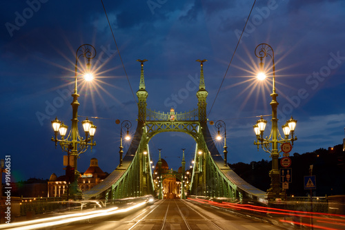 Liberty bridge with shining lanterns and moving traffic lights in Budapest night view