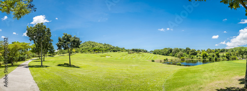 Papiers peints Herbe Green grass and trees at golf course with blue cloud sky background