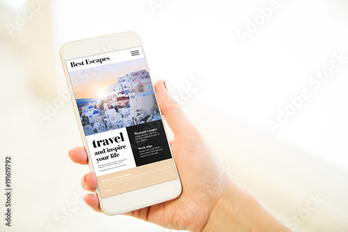 Fotobehang Santorini Woman holding a pink gold blank smartphone showing travel website