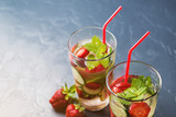Cold and refreshing infused detox water with strawberry and cucumber in glass on black background.