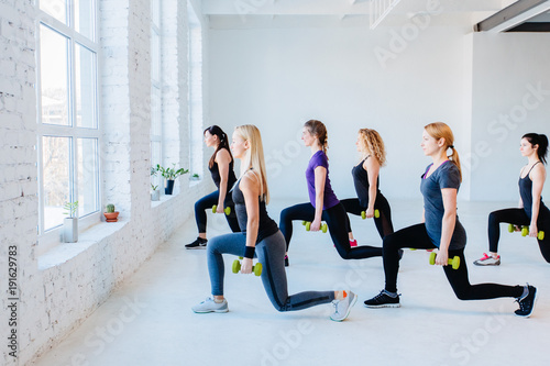 Leinwanddruck Bild Side view group of six athletic women doing lunge exercises with dumbbells in gym. Full height. Teamwork, good mood and healthy lifestyle concept.