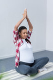 african american pregnant woman meditating with closed eyes and namaste mudra on yoga mat - 191630940