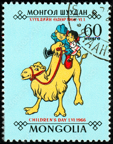 Fotobehang Kameel Ukraine - circa 2018: A postage stamp printed in Mongolia shows Children, a boy and a girl ride on a smiling camel. Series: Day of the child. Circa 1966.