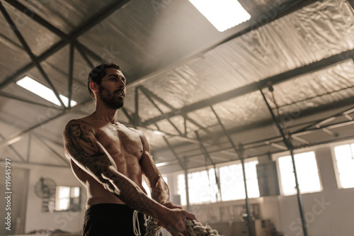 Sticker Muscular man exercising with heavy rope at gym