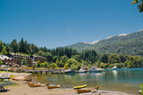 Beach in front of turquoise lake with yellow canoes, boats and pine forest in the mountains - 191649351