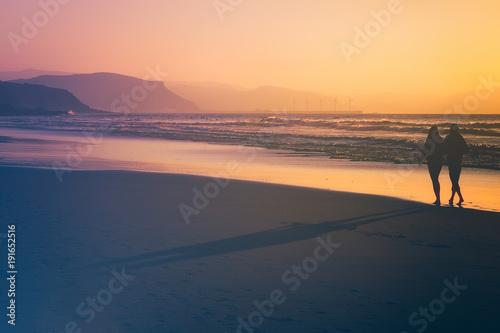 Foto op Aluminium Zee zonsondergang couple walking in the beach at the sunset