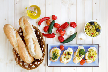 Bread rolls in basket with garlic, olive oil, peppers and couscous - with copy space
