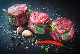 Raw beef fillet steaks mignon on dark background - 191656385