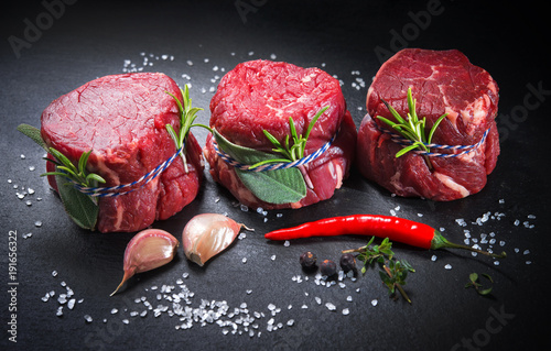 Raw beef fillet steaks mignon on dark background - 191656322