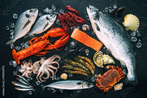 Fresh fish and seafood arrangement on black stone - 191656978