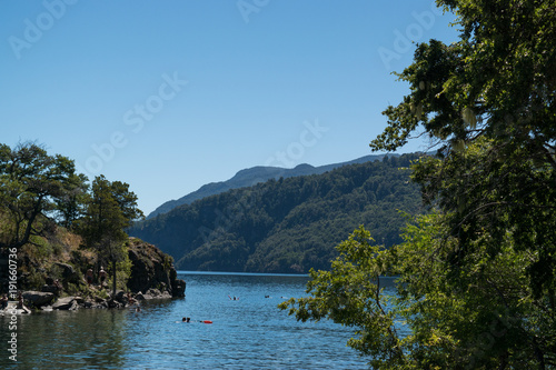 Landscape of a lake with an island, people swimming and mountains in the background