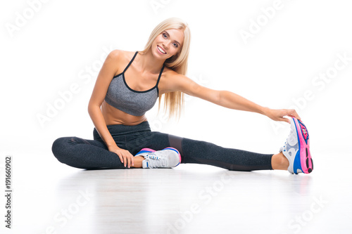 Plexiglas Fitness Young woman, doing stretching exercise at home or fitness studio