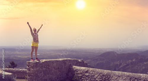 Keuken foto achterwand Aubergine A panorama of a happy young woman raising her arms to celebrate life and reaching the viewpoint after a hike