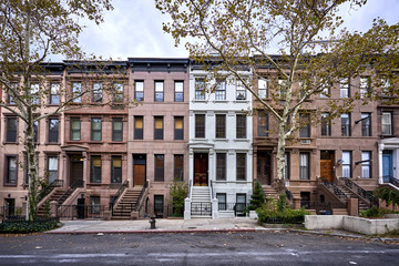 a view of a row of historic brownstone buildings in an iconic neighborhood of Manhattan, New York City